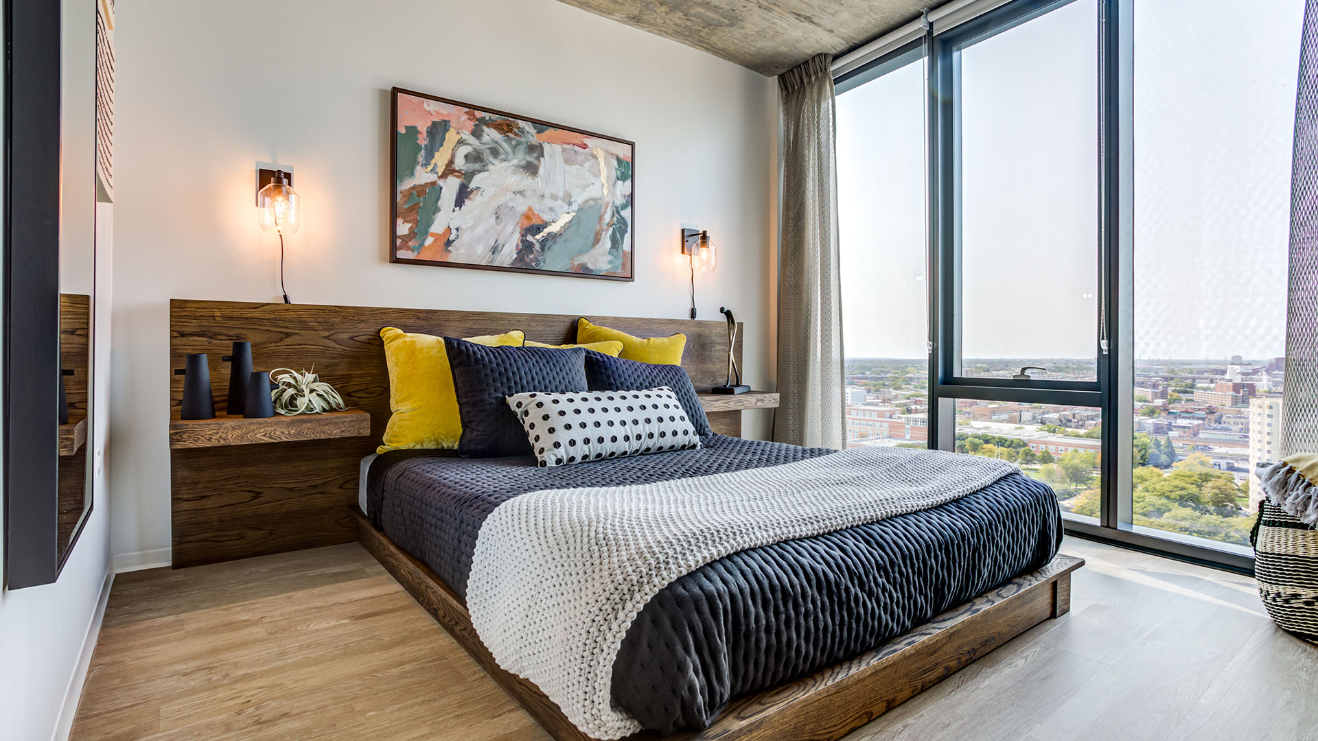 A bed with wooden headboard and end tables sits next to floor-to-ceiling windows, the city seen outside.