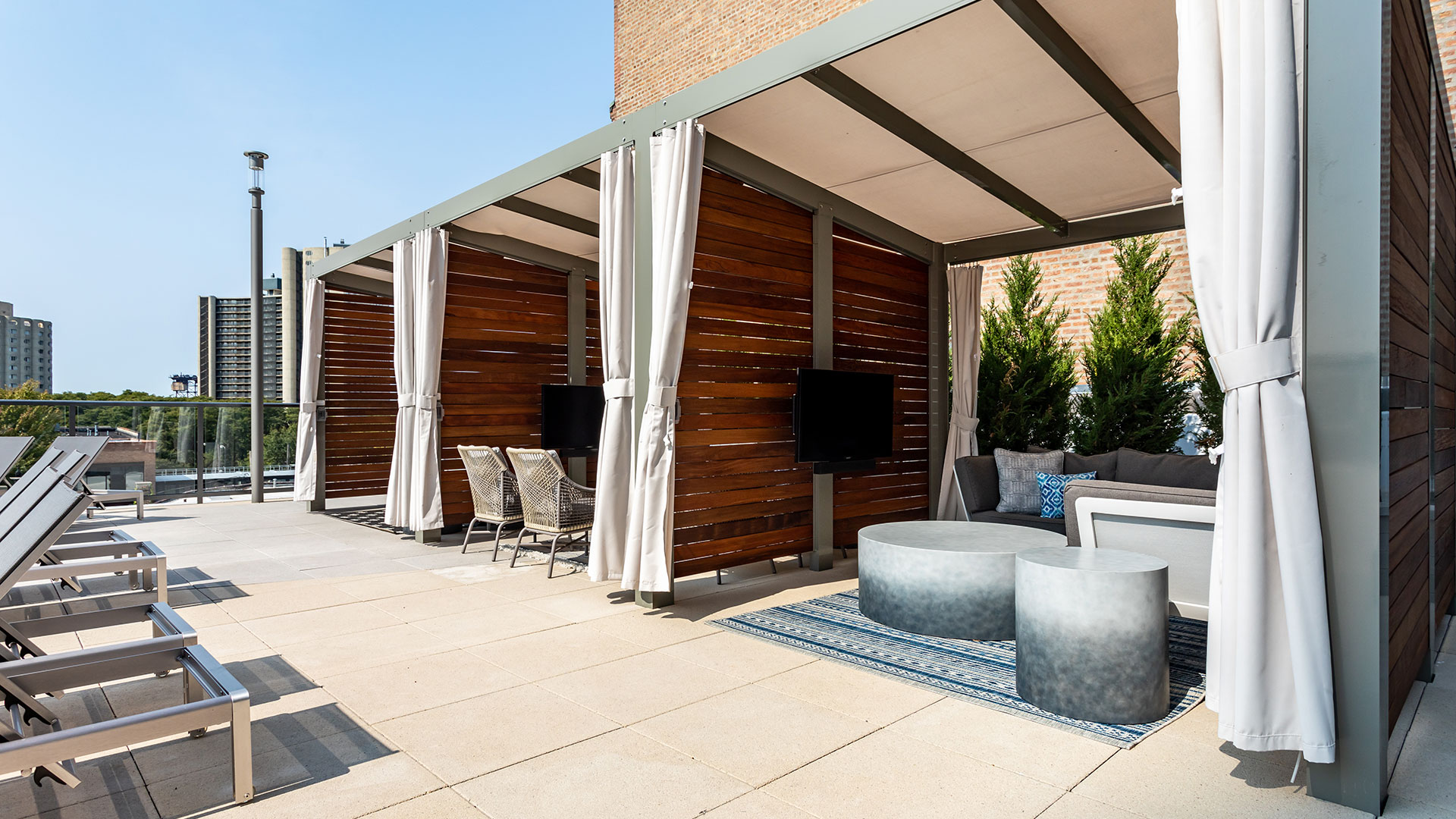 A row of private cabanas on the outdoor terrace. The curtains are open on each and furniture can be seen within each.
