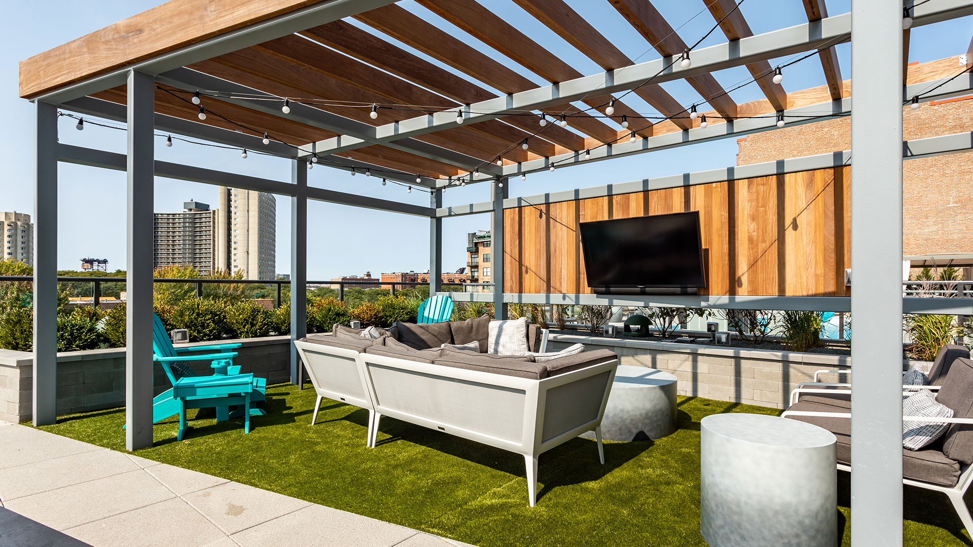A pergola sits over an outdoor furniture set and flat screen television.