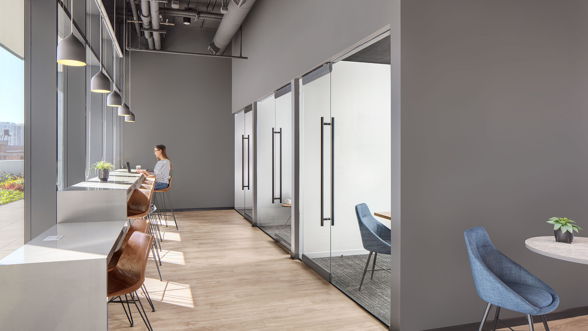 Looking down the row of private work spaces along the right, with glass doors and windows. Along the left open work spaces line the windows; a woman works near the end.