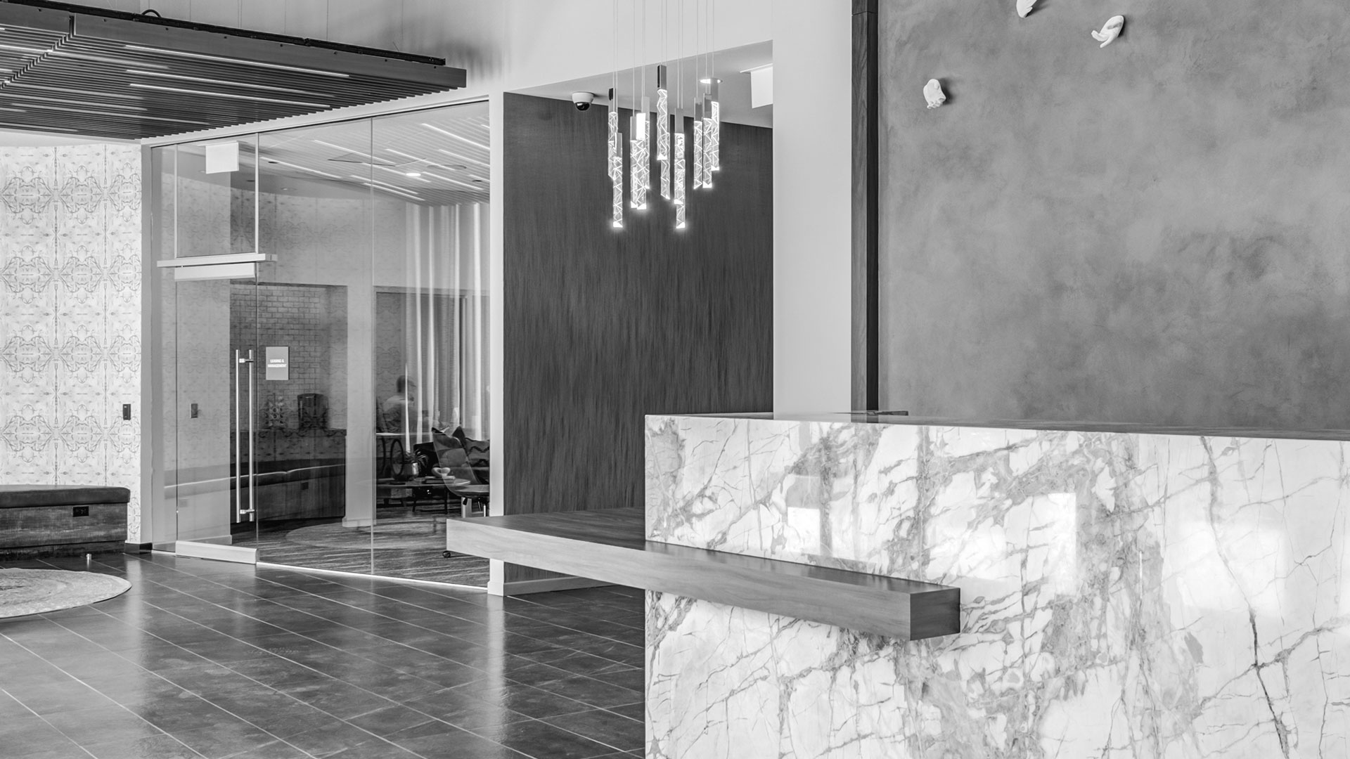 Looking through the lobby of Aspire Residences. A stone desk in the foreground with a modern light fixture above. Offices are seen in the background.