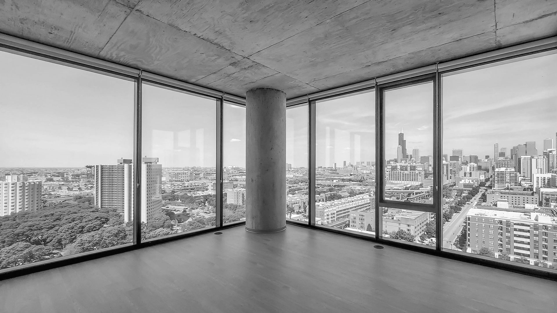An open room to show the concrete ceiling and the exposed concrete column in the center. Floor-to-ceiling windows are on each side with the Chicago skyline seen in the distance.